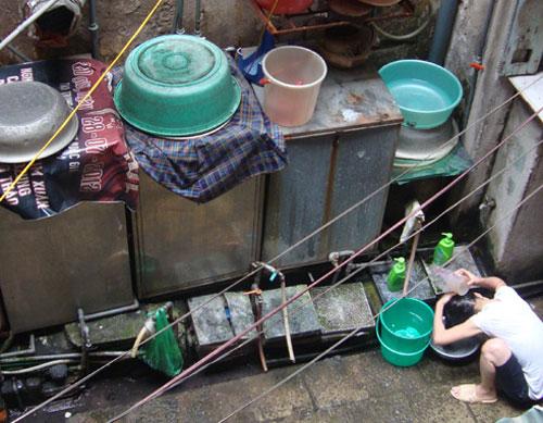Một cô gái gội đầu ở khu bể nước tập thể tại ngõ 15 Hàng Điếu. Dọc theo bờ tường là những máy giặt được để trong thùng, khóa lại cẩn thận bằng ổ khóa riêng - Ảnh: My Lăng