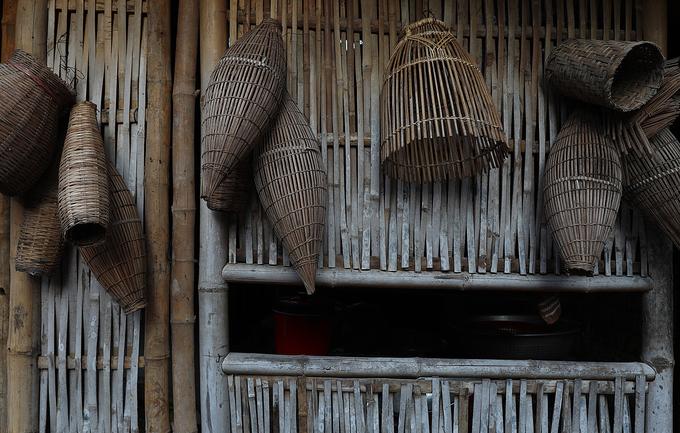 Những công cụ đánh bắt cá thô sơ trên bức tường (liếp) tre cạnh nhà.